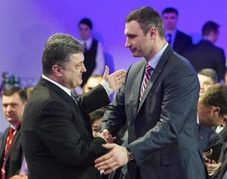 Ukrainian politician Vitali Klitschko (right) shook hands Saturday with Petro Poroshenko in Kiev after Klitschko withdrew from the presidential race to back Poroshenko.