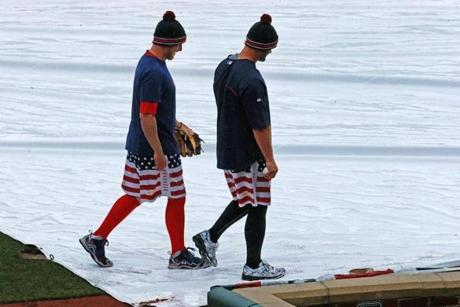 Mike Carp (left) and Ross walked past the tarpaulin covering the infield.