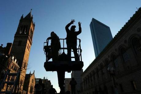 Photographer David L. Ryan directed the crowd on a lift at the Boston Marathon finish line on Boylston Street during the photo shoot.