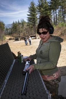 Karen Petitt, from Uxbridge, readies her shotgun for the range. They plan to take part in a turkey hunt at the former Fort Devens  on Monday.