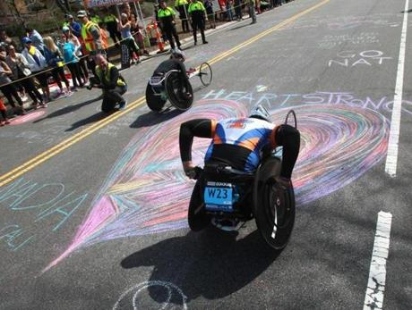 Wheelchair racers passed a giant chalk heart as they climbed Heartbreak Hill in Newton.