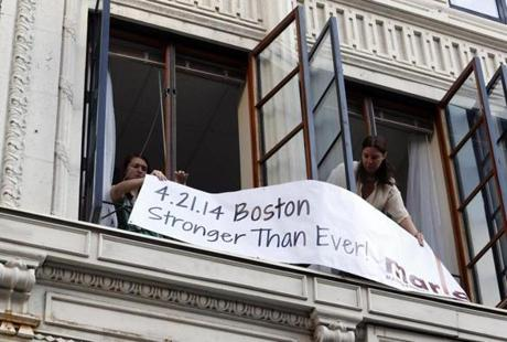 Women displayed a sign from a window above the site where the first bomb went off last year at the finish line.