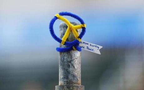 A peace sign topped one of the barricades near where the first bomb went off at the Boston Marathon last year.