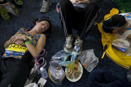 Hopkinton, MA - 4-21-14 - Meghan Dunn (cq) (left) relaxes with other charity runners for Children's Hospital before the start of the Boston Marathon at the Masonic Lodge in downtown Hopkinton. (Bill Greene / Globe staff)