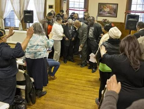 Clergy members gathered around the Rev. Bruce Wall at his Global Ministries Christian Church on Thursday. He read a statement saying he and an advisory group did nothing illegal in dealing with a rail company.