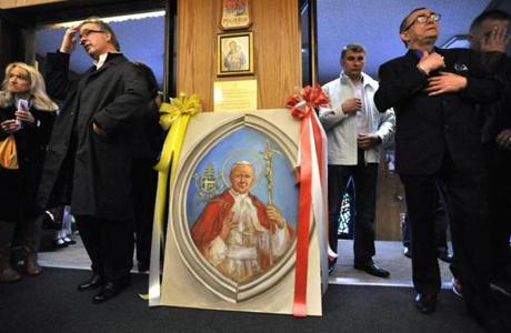 A portrait of Pope John Paul II stood by the entrance of Our Lady of Czestochowa in South Boston, as parishioners arrive for a Polish language mass celebrating the canonization of John Paul II.