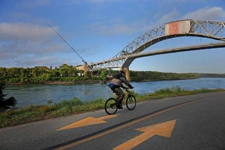 A fisherman pedals the bike path along the Cape Cod Canal past the Sagamore Bridge.