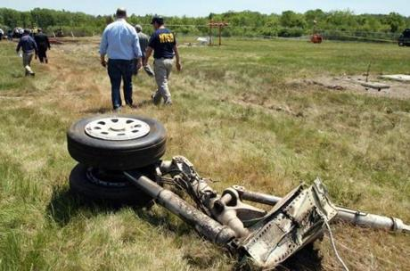 A National Transportation Safety Board official walkd away from a piece of the landing gear.