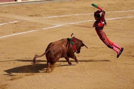 "Planting the ""banderilla:"" Matador El Fandi, currently ranked No. 1 among Spanish bullfighters, jumps in to stab the bull. The ""banderilla"" is the second step in the three-part modern bullfight, in which three pairs of colorful batons are attached to the back of the bull, and held in with barbed tips. It can be done by the matador or by one of the three ""banderilleros,"" also bullfighters, who form part of the matador's team."