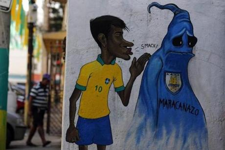 A man walks in Rio de Janeiro behind a graffiti depicting Brazilian soccer player Neymar and a phantom representing the Uruguayan soccer team, which won the 1950 World Cup.