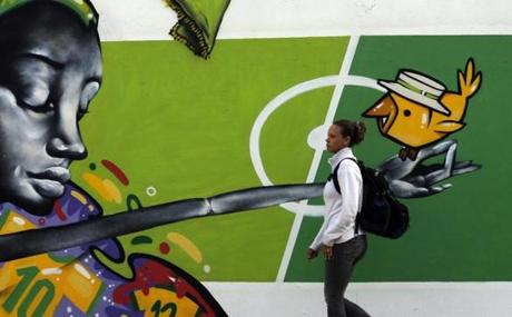 A woman in Rio de Janeiro walks past graffit about the 2014 World Cup.
