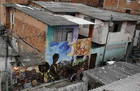 "A family walks past graffiti in reference to the 2014 World Cup, in the Vila Flavia slum of Sao Paulo May 28, 2014. The art is by members of OPNI, a Portuguese acronym which means ""Unidentified Graffiti Artists,"" was formed in 1997 as a means of transforming the streets in the slums into an open-air gallery where the group could express their gripes while also denouncing what they perceive as social injustice. Graffiti artists in Sao Paulo are using their art to take jabs at the establishment they believe have engaged in gross overspending in preparation for this year's World Cup in Brazil."