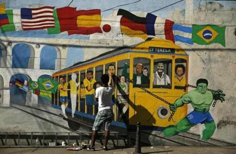 Brazilian artist Jambeiro paints graffiti in reference to the 2014 World Cup in Rio de Janeiro.