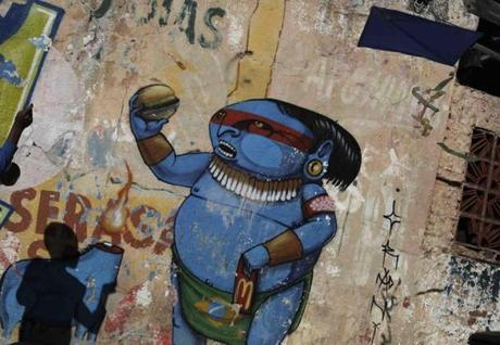 A boy prepares to fly a kite next to graffiti, by Brazilian artist Cranio, depicting an indigenous man, in reference to the 2014 World Cup, in Sao Paulo.