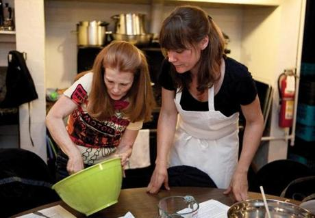 Susan Tinagero (near right) follows French pastry chef Yolene Adande's advice as she whisks ingredients for caneles.