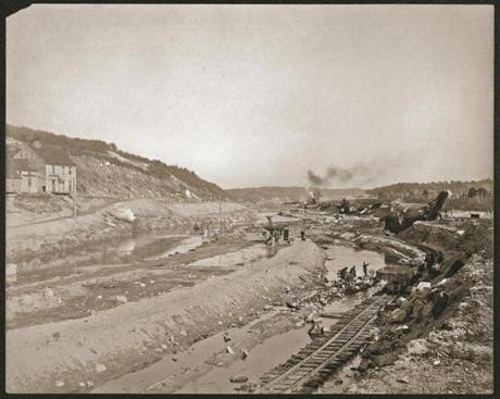 Some buildings were relocated for the project, but the farmhouse at far left had to be destroyed. Workmen load up a train car with boulders from alongside the railroad tracks.