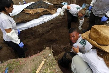 Xavier Colbert, 22, a senior at Baylor University, looked back at Lori E. Baker after pulling a body out of a grave with fellow members of the Baylor forensics team working to exhume bodies of unidentified migrants in Falfurrias, Texas.