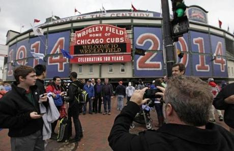 In this April 10, 2014 photo, fans arrive at Wrigley Field before a baseball game between Pittsburgh Pirates and Chicago Cubs in Chicago. Wrigley Field will host its 100th anniversary celebration as the Chicago Cubs host the Arizona Diamondbacks, exactly one century after the Chicago Federals opened then-Weeghman Park against the Kansas City Packers. (AP Photo/Kiichiro Sato) -- Baseballbucketlist