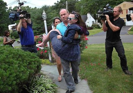 Justina was carried into her home by her father, Lou.