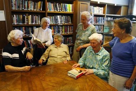 Lexington, Massachusetts -- 06/17/2014-- (L-R) Members of a book club Fran Spector, 83, Elizabeth Desan, 88, Polly Gardner, 87, Jacqueline Villars, 86, Lora Lee Buchta, 82, and Davette Abkowitz, 90, pose for a photograph at their retirement community's library in Lexington, Massachusetts June 17, 2014. Jessica Rinaldi/Globe Staff Topic: Nursinghomebookclub02 Reporter: Nicole Lamy
