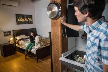Matthew Knoll stood in the kitchen area while his girlfriend, Emily Wu, played with their dog in the bedroom of the 451-square-foot home at Factory 63.