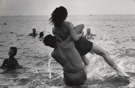 A swimmer at Coney Island tosses his girlfriend into the water in this 1952 shot by Garry Winogrand.
