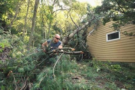 Michael Aceto removed a pine branch outside a home on Hemlock Lane in Bedford.