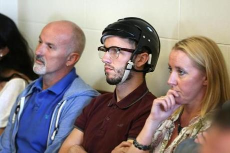 Dylan Fitzgibbon, sitting with relatives, wore a helmet to protect his head at the arraignment of John Rogaris. Fitzgibbon's lawyer says he will undergo surgery.