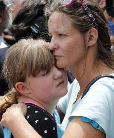 Geri Boyles of Lowell hugged her daughter, Corinna, outside the building.