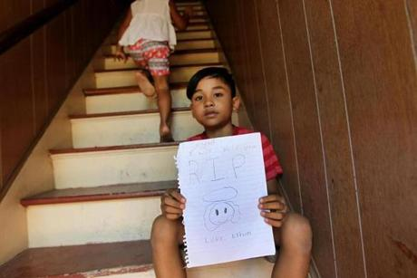 Ethen Lam , 7, who lives down the street, mourned his cla