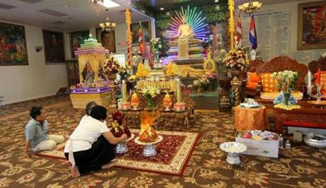 Members of the temple prepared the monk's daily offering in front of the altar.