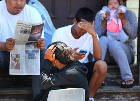 Resident s of a nearby building sit on their front steps as they read the news about the fire.