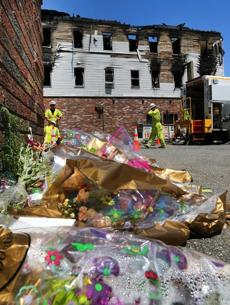 Flowers were left  Friday next to a building on Branch Street that was the scene of an apartment complex fire that killed seven.