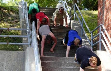 People in Parkour classes crawl down stairs or lift themselves using a column of a building.