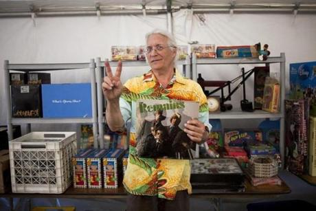 "7/12/14 Brimfield, Mass. Gary ""Wex Rex"" Sohmers holds a record of the band ""The Remains"" in his booth at the Brimfield Flea Market on Saturday evening, July 12, 2014 in Brimfrield, Mass. ""The Remains are from Boston,"" he says, ""They actually used to open for The Beatles when they would come into town."" (Zack Wittman for the Boston Globe)"