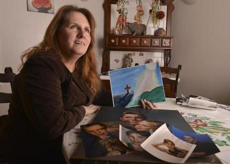 Lisa Brown, the mother of Joshua Messier, reminisced about her son as she held a copy of a painting he made. Messier was a young mental health patient who died as Bridgewater State Hospital guards were forcibly subduing him and putting him in restraints.