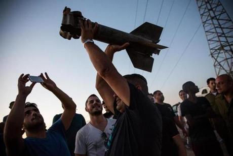 In Sderot, Israel, a man held up a destroyed rocket, which he said was fired from inside Gaza toward Israel.
