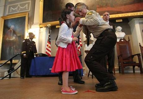 Aileen McLoughlin got some help pinning her badge from five-year-old daughter Morgan.