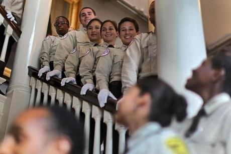 Smiling EMT graduates lined a stairway for a photograph.