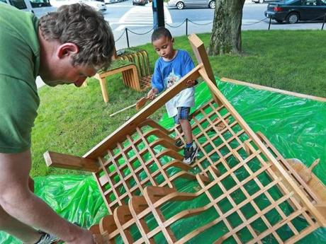 Derek Rieman (left) and 4-year-old Adrias Tanner paints a part of a structure for the parklet being built on a side street near 506 Park Drive.