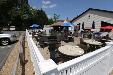 At Mia Regazza, a white Chestnut Hill-style fence encloses an outdoor patio next to a parking lot.