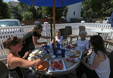Mia Regazza waitress Dawn Kelly serves the Corcoran Family from Whitman on the restaurant's outdoor dining area.
