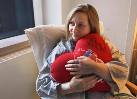 "Boston, MA 011012 Patient Amy DeStefano (cq) of Portsmouth, N.H., who received the first ""beating heart transplant,"" held a ""heart"" pilow, given to her by the staff, while recuperating at MGH in Boston, Tuesday, January 10 2012. (Globe Staff Photo/Wendy Maeda) section: Metro slug: 11heartreporter: Liz Kowalczyk Library Tag 01112012"