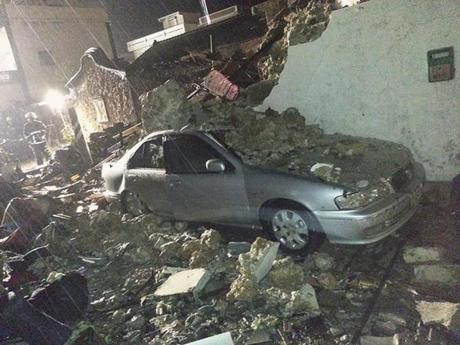 A car was covered in rubble from the wreckage.