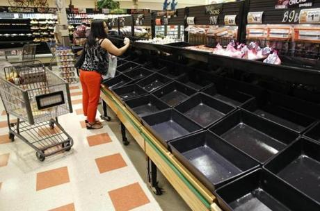A shopper examines produce near empty bins in a Market Basket grocery store.
