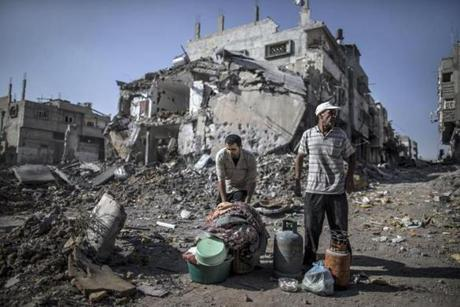 Palestinian men gathered things they found in the rubble of destroyed buildings in a Gaza City district.