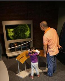 Tourists Grace Huang, 3½, and her father, Sheng Xi Huang, at a station where children can turn a dial to view our sun.