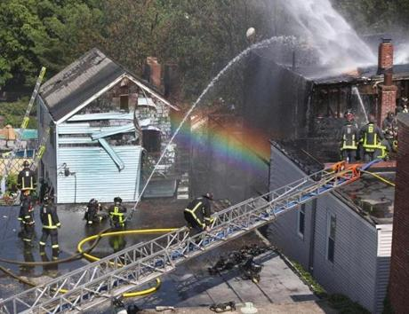 Sunlight created a rainbow as firefighters poured water on the roof of 309 Sumner Street in East Boston.