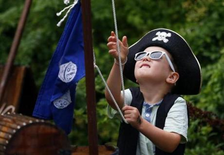 Hudson Wynne, 4, of Beverly looked up as he tried to raise his flag the fastest during a game at the New England Pirate Faire in Salem.