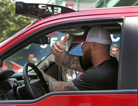 Jonny Gomes gave a thumbs up as he drove away from Fenway Park.